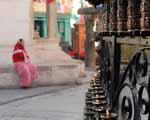 Candles, Prayer Wheels, Woman in Red and Pink